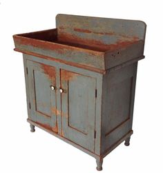 19th century Pennsylvania Drysink with original wonderful worn dry blue paint, with two panel doors which are mortised and pegged, natural patina interior, solid board ends with a cut out foot, dovetail well. circa 1820