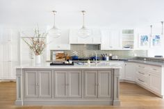 Traditional kitchen design with an island in contrasting gray with a marble countertop tied together with gray Caesarstone and a smokey gray backsplash. Featuring Rose City pendant lights by Rejuvenation.