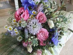 Bridesmaid's bouquet of blue and pink pastel coloured country garden flowers