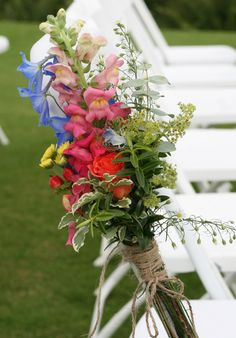 Rustic pew end of beautiful bright blooms for a July wedding at Wedderburn Castle. Contact The Stockbridge Flower Company, Edinburgh for more details