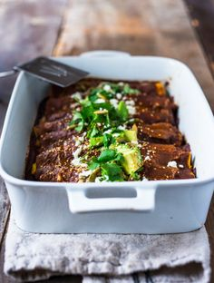 Roasted Butternut Mole Enchiladas with Blackbeans - topped with cilantro, avocado and toasted sesame and pumpkin seeds. An easy delicious vegetarian main. | www.feastingathome.com