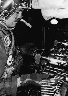 A Fairchild AC-119G gunner loads ammunition into a minigun, during the Vietnam War. U.S. Air Force photo