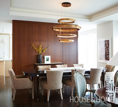 For a more contemporary aesthetic, designer Neil Johnson stained an antique cherry dining table a few shades darker and paired it with a sculptural brass chandelier. | Photo: Angus Fergusson