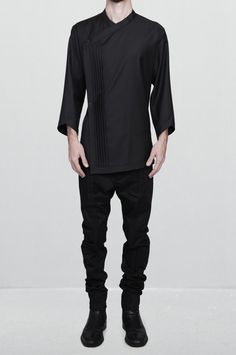 This peculiar asymmetric shirt is crafted from a sheer fine wool inthe nuance of Iron-black to steel-gray graphite mineral. The textureof the fabric has a gentle silky gleam forming one rakishmanner. The closure is located in the front right part and is madewith two oxidized silver buttons. On the crossing point of the sidesaround the neck lies a lightweight magnet for invisible attachment.The emphasis of this artefact is in five identical pleats attached inthe front right part creating one…