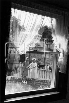 Two girls playing with cats in a garden, USA (Edouard Boubat, 1979)