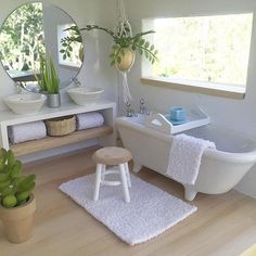 The bathroom area in the Whimsy Luxe. I love the big windows, they really brighten the room plus they're fun to look in through. The sills are wide enough for planters and other decor. This photo also features our double vanity with mirror, tiny tray, wooden stool, hanging plant and free standing tub. All will be in stock next month.