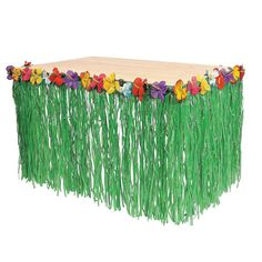 Dress your luau party tables with this green grass table skirt with hibiscus lei border! Made of plastic and polyester fibers, this table skirt is