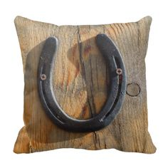 A charming Western equine good luck charm pillow. Big lucky horseshoe in a cowboy or cowgirl rustic style decor. Custom accent pillow with a removable pillow case or pillow cover. Western knotty wood grain look. PHOTOGRAPH of real wood art at the ranch looks 3-dimensional! Used lucky horseshoe is screwed to slab of weathered pine wood. Shadows cross the cracked wood with knots. Horseshoe from one of the happy horses living with She Wolf Medicine. Depicts ranch life, country living, rural…