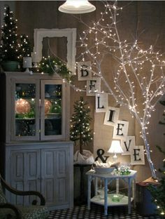 Beautiful Christmas decor made with tree branches spray painted white & little white Christmas lights. The little lamp on the table helps to accent the whole scene.