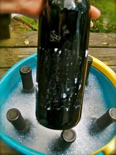 How to remove labels from wine bottles:  1. Soak wine bottles in a bucket of cold soapy water for several hours.    2. Scrape away label with fingernails.    3. Use an old sponge to remove the rest of the label.