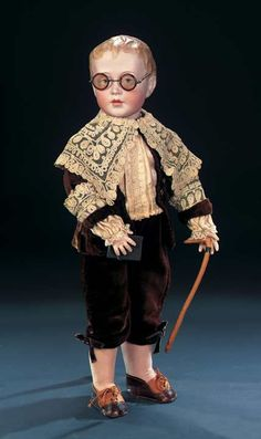 """German Bisque Art Character Boy,153,by Simon and Halbig,known as 17""""- Antique costume comprising brown velvet jacket and short pants in the Little Lord Fauntleroy style with silk shirt,lavish antique collar,knit stockings and leather saddle shoes,and with faux-horn rim spectacles and wooden walking stick. Condition: generally excellent. Marks: 153 S&H 7. Comments: Simon and Halbig,circa 1910"""