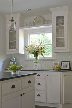 Kitchen with display and window looking out elegant not over the top traditional kitchen by Sarah Greenman
