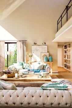 Salón a doble altura con luz natural, ventanas con cortinas ligeras, sofá capitoné y mesa de centro de madera.