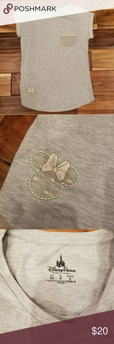 Disney Parks Minnie Mouse One Pocket Tee Disney Parks Minnie Mouse One Pocket Tee. Great condition. Perfect for a trip to Disney Amusement Parks. Has one pocket covered in polka dots. A Minnie Mouse is embroidered in the lower corner. It's sleeves are rolled up and stitched that way. No trades, offers welcomed! Enjoy! Disney Tops Tees - Short Sleeve