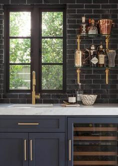Gorgeous wet bar features dark blue shaker cabinets adorned with brushed brass hardware paired with white marble countertops and a glossy black tile backsplash.