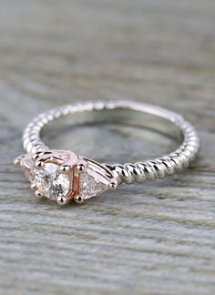 A custom made Two-Tone Twisted Rope Trillion Diamond Engagement Ring in White & Rose Gold!