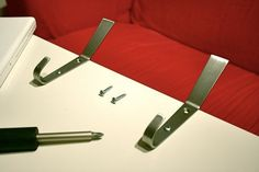 Two wall hooks are repuposed as a fixed laptop stand.