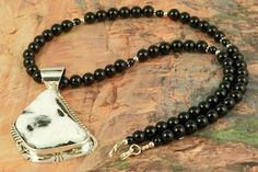 Genuine White Buffalo Turquoise set in Sterling Silver Pendant on a Genuine Black Onyx Necklace with Sterling Silver Beads and Clasp. This Beautiful Stone is formed from the minerals Calcite and Iron. It is mined near Tonopah Nevada. Created by Navajo Artist Phillip Sanchez. Signed by the artist.