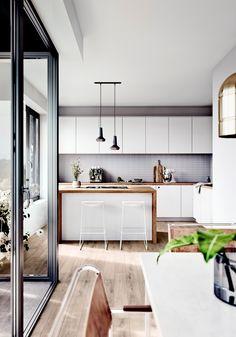 Moderne und offene Wohnküche im Neubauprojekt OASIS Berlin in Tiergarten, Weiße Küche mit einer Arbeitsplatte aus Holz, Kochinsel, Küchenideen, Neubau Küche,, Helle Küche im Neubau