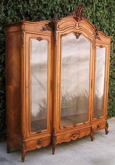 A Large and Impressive French 19th Century Finely Carved Walnut Three-Door Armoire/Vitrine. The converted vitrine with three front doors, th...