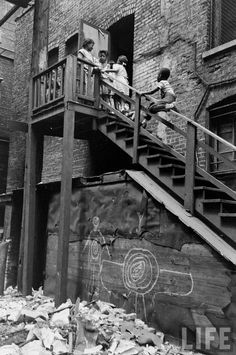 Wee8 nothing much has change this is a picture of 1954 and the south of Chicago still has buildings in this condition children playing in unsafe areas with no clean Grass    U.S. Chicago, 1954 // By Fritz Goro