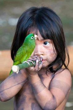 enfant amazonien avec perroquet vert sur bambou