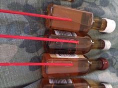 Hot glue wooden sticks to the back of the mini liquor bottles. Don't worry if the bottles are plastic, they shouldn't melt.
