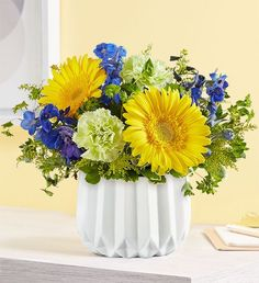 Capture the essence of summer with our Coastal Garden™ flower arrangement. A gathering of yellow Gerbera daisies, pops of blue delphinium and assorted greenery, hand-designed in our geometric vase. These summer flowers are the perfect addition to any occasion this summer. Summer Flowers To Plant, Month Flowers, Planting Flowers, Blue Delphinium, Preserved Roses, Coastal Gardens, Local Florist, Hand Designs, Lush Green