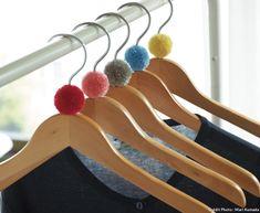 À l'aide de fils de couleur, suivez le tuto de Maison Créative pour créer des pompons et décorer des cintres en bois.