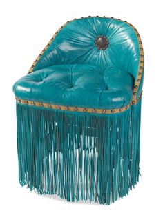 a low silhouette in vibrant, turquoise leather with deeply tufted seat, concho back, lavish fringed skirt and grand nail head trim.