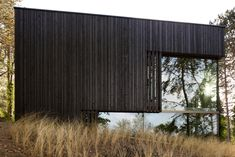 Charred timber and glass villa by VVKH Architecten is embedded in a dune