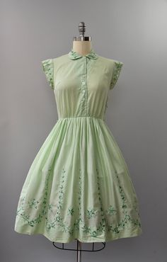 Just perfect 1950s minty green cotton shirtdress with nipped waist, full pleated skirt with ombre green floral embroidery across the hem, matching cap sleeves, small turn down collar, buttons up the front bodice and hidden metal side zipper. Unlined. condition: overall excellent, some very minor seam stress on the bodice. freshly cleaned and ready to wear label: none material: soft lightweight cotton (semi sheer) ----✄----Measurements----✄---- bust: 36 in waist: 28 in shoulder to waist: 15…
