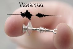 "3D-printed silver earring in the shape of a sound wave recorded while a person is saying ""I love you."""