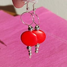 A pair of wire-wrapped earrings featuring red circle beads and some silver beads.