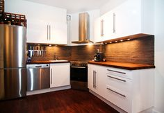 Small kitchen situated in corner of room with white cabinets and dark brown back splash.