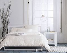 Bedroom: Modern white side tables, tall branches, and low-hanging industrial lamp can mix with antique bed