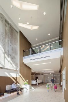 The main entry lobby of Stanford Cancer Center South Bay features floating lights, warm wood, and delicate textural artwork. Photo: © Kyle Jeffers