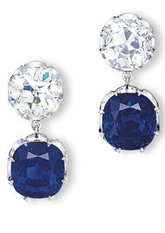 AN EXQUISITE PAIR OF SAPPHIRE AND DIAMOND EARRINGS Each set with a cushion shaped sapphire weighing 8.74 and 8.65 carats, to the old mine-cut diamond surmounts, mounted in platinum, 2.8 cm long