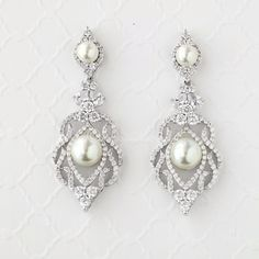 These divine earrings are ideal for weddings or any other elegant affair! They feature a splendid Art Deco-inspired design of crystal clear cubic zirconia and off-white glass pearls. They are 2.25 inc