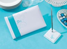 "Unik Occasions - Lillian Rose Aqua or Pink Floral Guest Book with Pen Set This set is covered in white satin. The 3.25"" pen base holds a silver pen with black ink. Both the pen base and the 10"" x 6.5"" guest book cover are silkscreened with an aqua floral design of swirls, dots, leaves and flowers. An aqua satin ribbon wraps around the cover of the guest book, which contains 30 two-sided pages for a total of 580 signatures. Price $27.00"