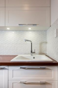 Lavare Laundry Renovation features ceramic laundry sink and a hexagonal feature tile splashback