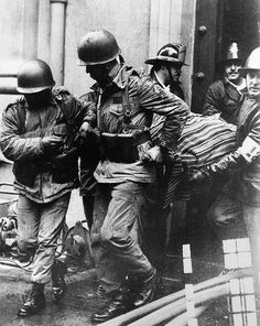 Soldiers and firefighters carry the body of President Salvador Allende, wrapped in a Bolivian poncho, out of the destroyed La Moneda presidential palace, after the 1973 military coup led by Gen....