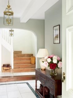 How gorgeous is this entryway. Soft Gray walls and a pretty wood staircase. Lovely pink, red and white flowers.