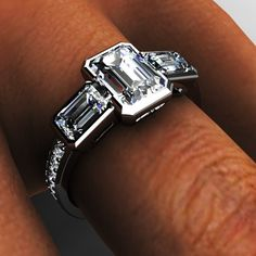Platinum three stone emerald cut diamond bezel engagement ring