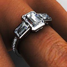 Platinum three stone emerald cut diamond bezel engagement ring