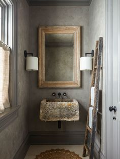 """The rough-hewn stone sink is the star of the powder room. """"It was something the owner had found in France when she was on vacation,"""" says Greene. Gray Venetian plaster walls contrast with a little linen cafe curtain on the window, which overlooks the front porch; the mirror and ladder are finds from the Brimfield Antique Show."""