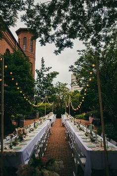 Lights strung over long farm tables   Jessica Love Photography