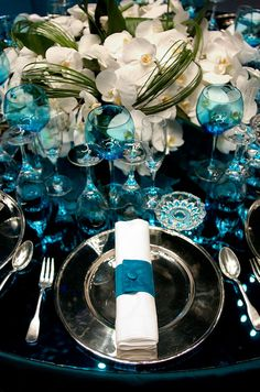 A lush floral centerpiece of crisp whitephalaenopsis orchidsatop an aqua color mirrored tabletop is truly chic.