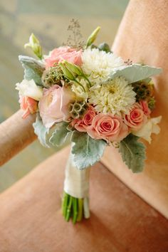 vintage chic floral arrangement: dusty pink garden and spray roses, cream dahlias, scabiosa pods, grey dusty miller and seeded eucalyptus for the arrangements set in vintage bottles and mercury glass vases.