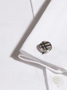 A crisp white shirt finished with a set of classic yet contemporary Burberry cufflinks.
